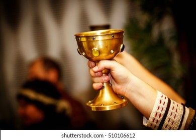 Golden cup in hand on a medieval feast