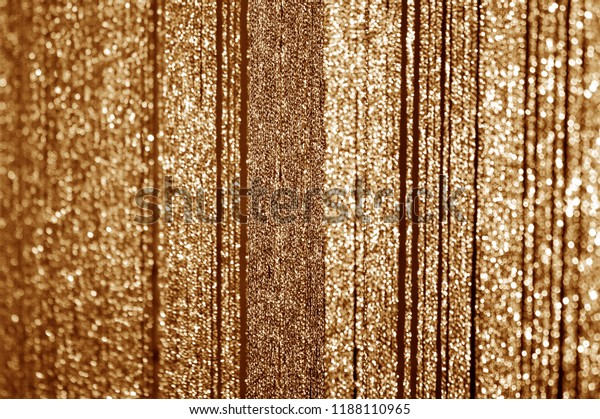 Golden curtains made of shiny threads. Abstract Christmas or New Year blurred background.