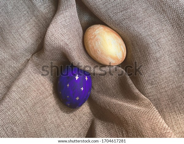 Golden and dark blue Easter eggs isolated on a natural linen textile background with copy space. Two dyed Easter eggs on vintage textile, top view, flat lay.