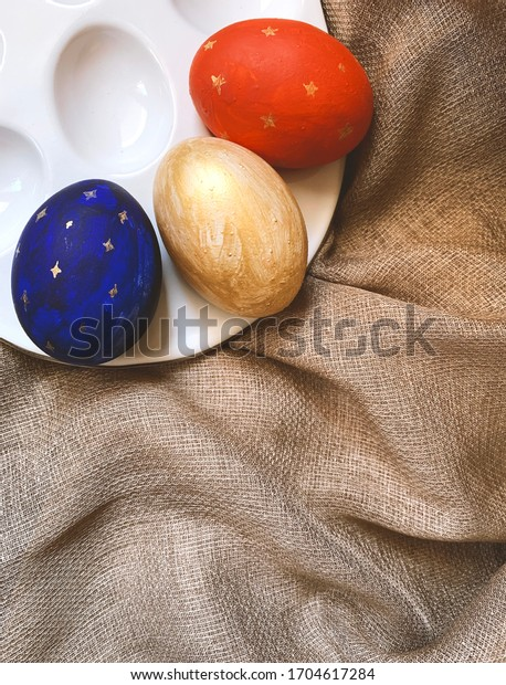 Golden, dark blue and red Easter eggs on a plate, isolated on a natural linen textile background with copy space. Three dyed Easter eggs on vintage textile, top view, flat lay.