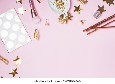 Golden decor and feminine accessories on the pink background, top view