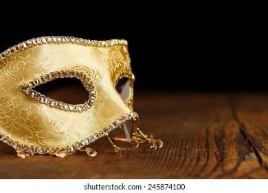 Golden decorated Venice mask on rustic wooden table