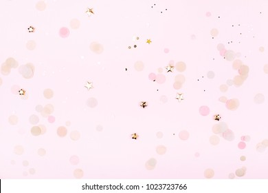 Golden decorations on pink pastel background. Top view. Festive greeting concept.