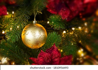 Golden decorative ball hanging on a branch of a Christmas tree in the light of a golden garland. Phot backdrop decoration for Christmas design. Festive banner postcard flyer copy space