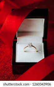 Golden diamond engagement ring placed in black box with red docorative ribbon.