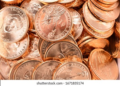Golden Dollar USA coins close up including Sacagawea and Presidential coins. Use as background. Brilliant uncirculated coins show off their golden shades of newly minted metal and edge lettering.