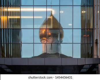 Golden dome at evening of the Orthodox Church is reflected in modern architecture