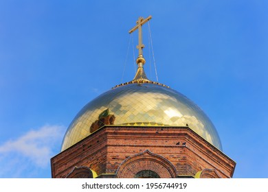 The golden dome of the old brick church. Close-up, bottom view. Sunny day and blue sky. The sun reflects on the golden surface of the dome. Ancient rural church in traditional style. Ural (Russia)