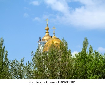 Golden domes with crosses of Savior-Transfiguration Cathedral behind the crowns of trees against blue sky (Sumy, Ukraine). Old dome with shabby paint of an orthodox temple, background with copy space