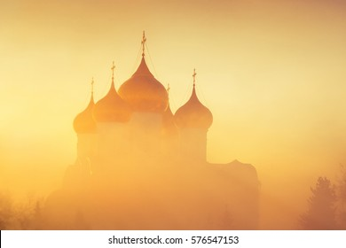Golden domes in fog in sunlight as background. Winter frosty misty morning. Church in fog in background of rising sun.