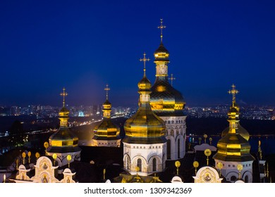 Golden domes of Kyev-Pechersk Lavra at night with blue sky on the background in Kyiv, Ukraine. Long exposure shot of Kyivo-Pechers'ka Lavra cathedral in Kiev. Golden bright domes of church at nights.