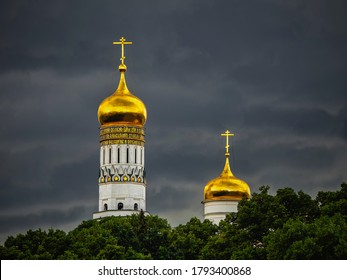 Golden domes of the old Cathedral in the Moscow Kremlin before a downpour.