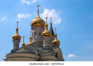 Golden domes of Orthodox Cathedral in Donetsk, blue sky in the background
