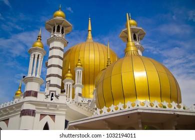 Golden domes of Ubudiah Mosque with blue sky background in Kuala Kangsar, Perak, Malaysia.