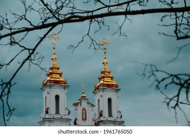 The golden domes of the white church against the blue sky. Religion. The Orthodox Church. Christian holiday.