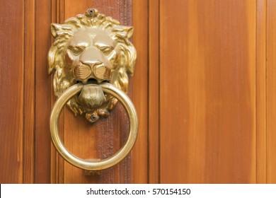 Golden door knocker in the shape of lion with ring on a wooden door