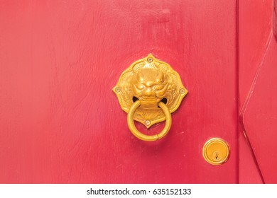 Golden door knocker in the shape of lion with ring on a red wooden door. Close up wooden Chinese style red door with lion head doorknob.