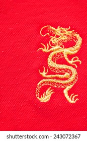The golden dragon in golden thread sewed on the red fabric.