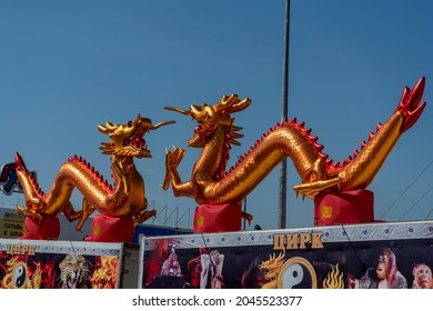 Golden dragons on the fence of the circus. Russia, Krasnoyarsk July 2021. Circus in the city against the blue sky.