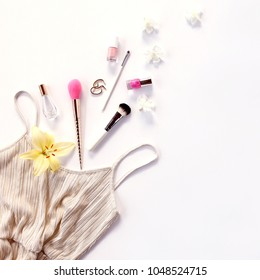 Golden dress and feminine accessories on white background