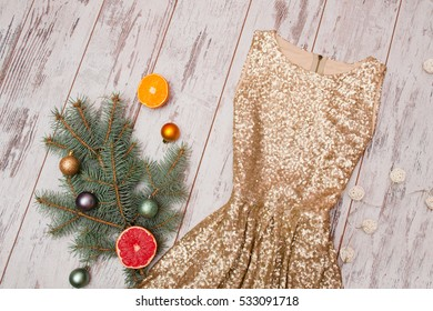 Golden dress with sequins on a wooden background, spruce branch and balls and citrus