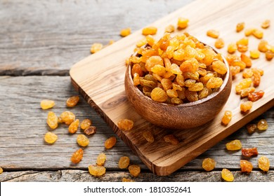 Golden dried raisins in wooden bowl on a wooden table.