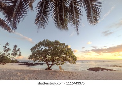 Golden dusk sun light at sunset on beautiful empty tropical beach with deckchair and palm tree fronds at Lefaga, Matautu, Upolu Island, Western Samoa, South Pacific