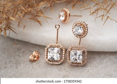 Golden earrings isolated, with white crystals and diamonds. Beautiful earrings on white background. Women accessories
