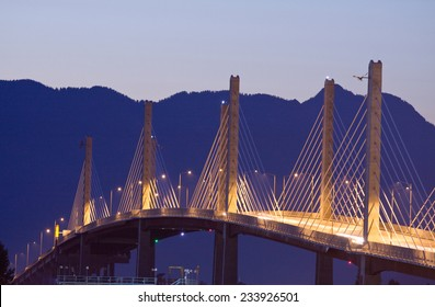 Golden Ears Bridge lit up at night. Coast Mountains behind.