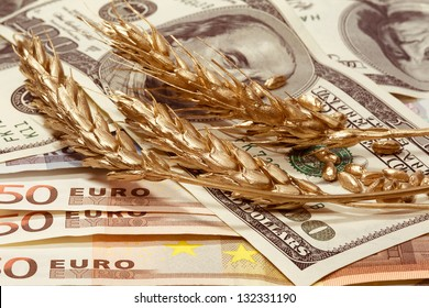 Golden ears of wheat on the dollar and euro banknotes