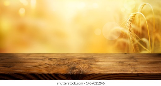 Golden ears of wheat with rustic wooden table for a thanksgiving decoration