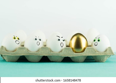 Golden egg among agressive, angry white eggs in a paper tray. Hate in group, jealousy, xenophobia concept.