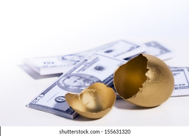 A golden egg cracked open sits in front of some money.