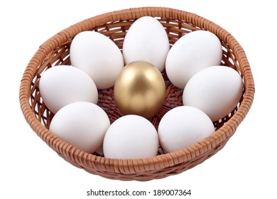 Golden egg and jast eggs in wicker bowl on a white background