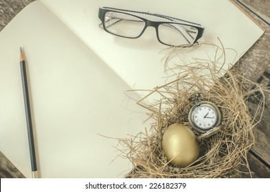 golden egg, pocket watch in the nest, notebook,glasses, pencil over wooden background