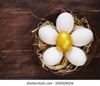Golden egg and white eggs on a wooden background