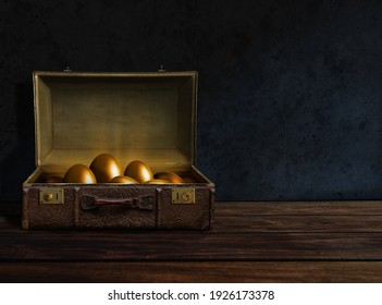 Golden eggs inside an old suitcase