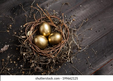 Golden eggs in nest on dark vintage wooden background