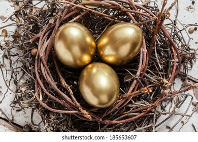 Golden eggs in nest on white vintage wooden background