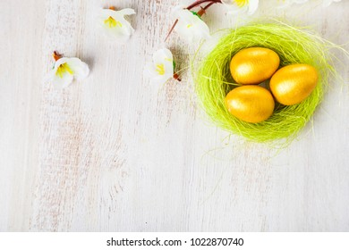 Golden eggs in a nest on a wooden background. Easter still life with flowers, nest and eggs.