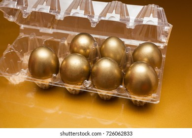 Golden eggs in a plastic box on golden background