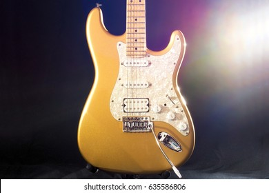 golden electric guitar on dark background. Musical instrument for rock, blues, metal songs.