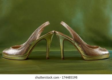 Golden elegance shoes  on green silk background