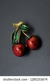 golden enamelled brooch sweet cherry isolated on black