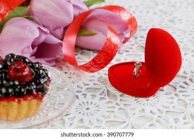Golden engagement ring in a heart shaped box, berries cake and a flower tulips