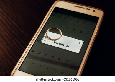 golden engagement ring on phone with calendar with wedding day. time for wedding