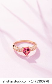 Golden engagement ring with pink heart shaped gemstone on pastel background. Wedding fashion jewelry
