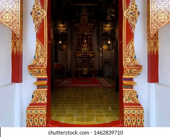"""A golden entrance gate of Thai traditional buddhism style temple with decoration by gold on red """"Thai Arts"""" or """"Line Thai"""""""