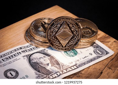 Golden Ethereum and Bitcoin coins on a one Dollar bill on a wooden surface with a black background.