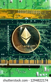 Golden Ethereum coin lying on computer motherboard, cryptocurrency investing, blockchain technology concept